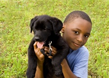 Boy holding a black puppy, both sitting in grass